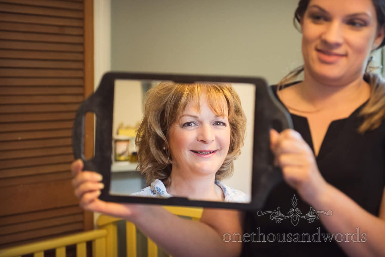 Mother of the bride in mirror on wedding morning