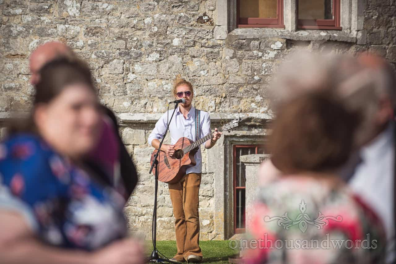 Musician performs in garden during woodland Lulworth Castle wedding