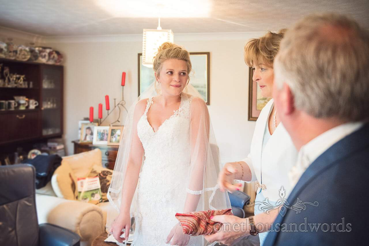 Nervous looking bride with parents on wedding morning