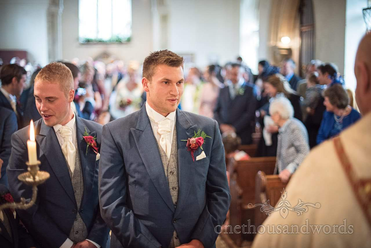 Nervous looking groom at the alter waits for his bride to be
