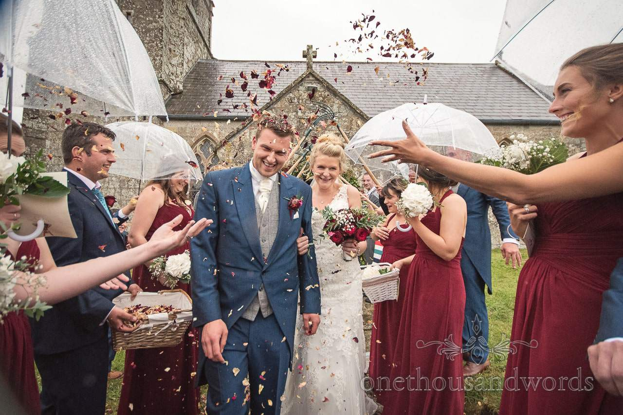 New Mr and Mrs brave confetti and rain shower from farm marquee wedding photos