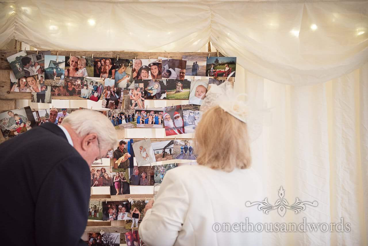 Old photo memories pegged to a wooden frame at marquee reception