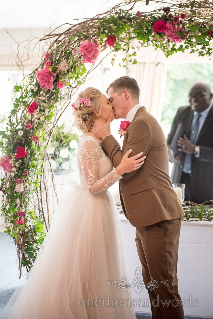 Sealed with a first kiss under flower arch at Italian Villa wedding
