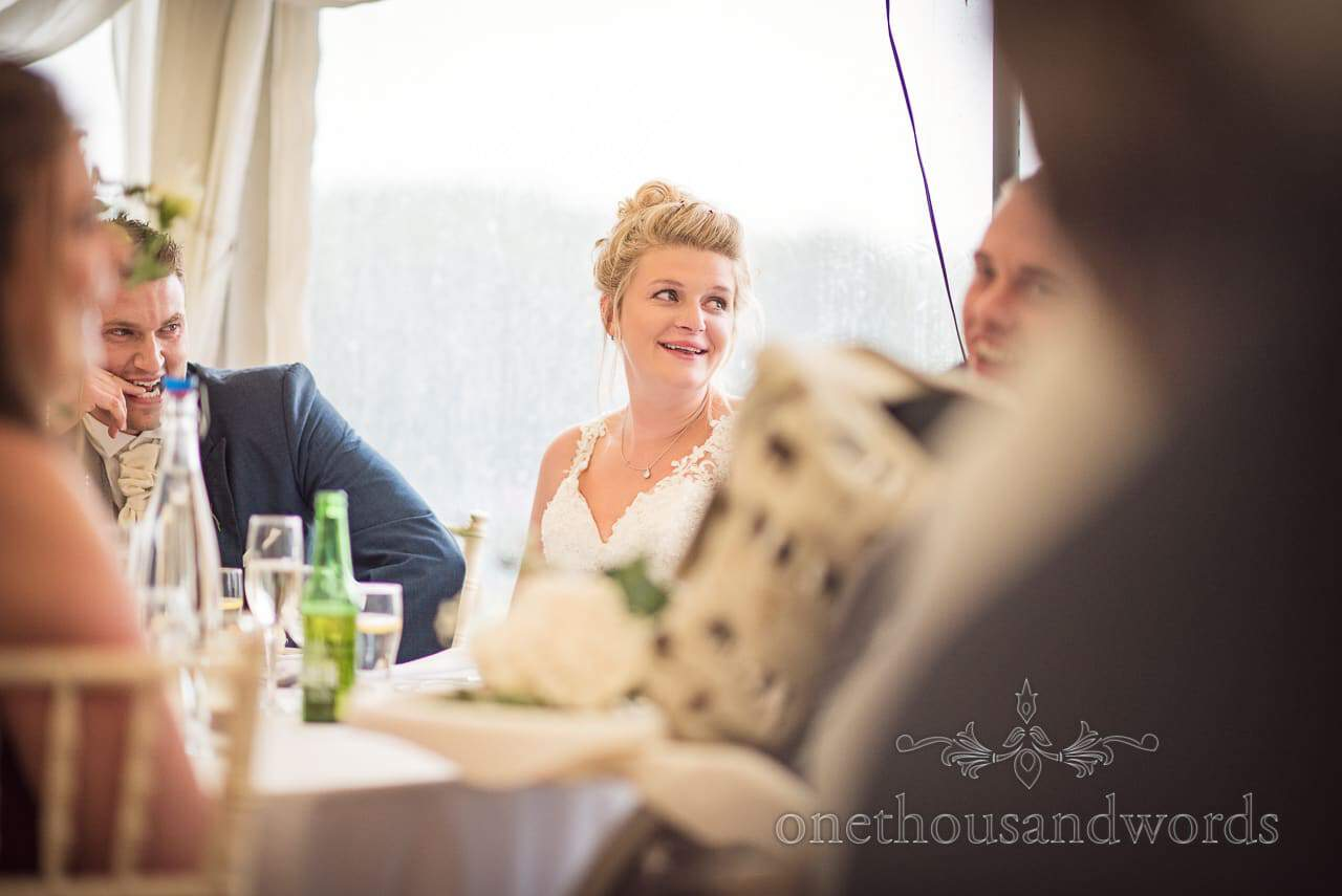 Smiling bride during speeches at farm marquee wedding reception