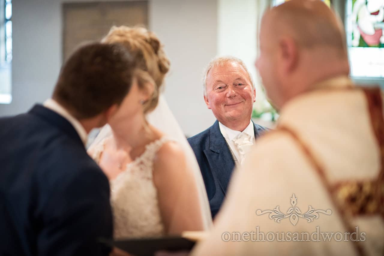 Smiling father of the bride as newlyweds have first kiss