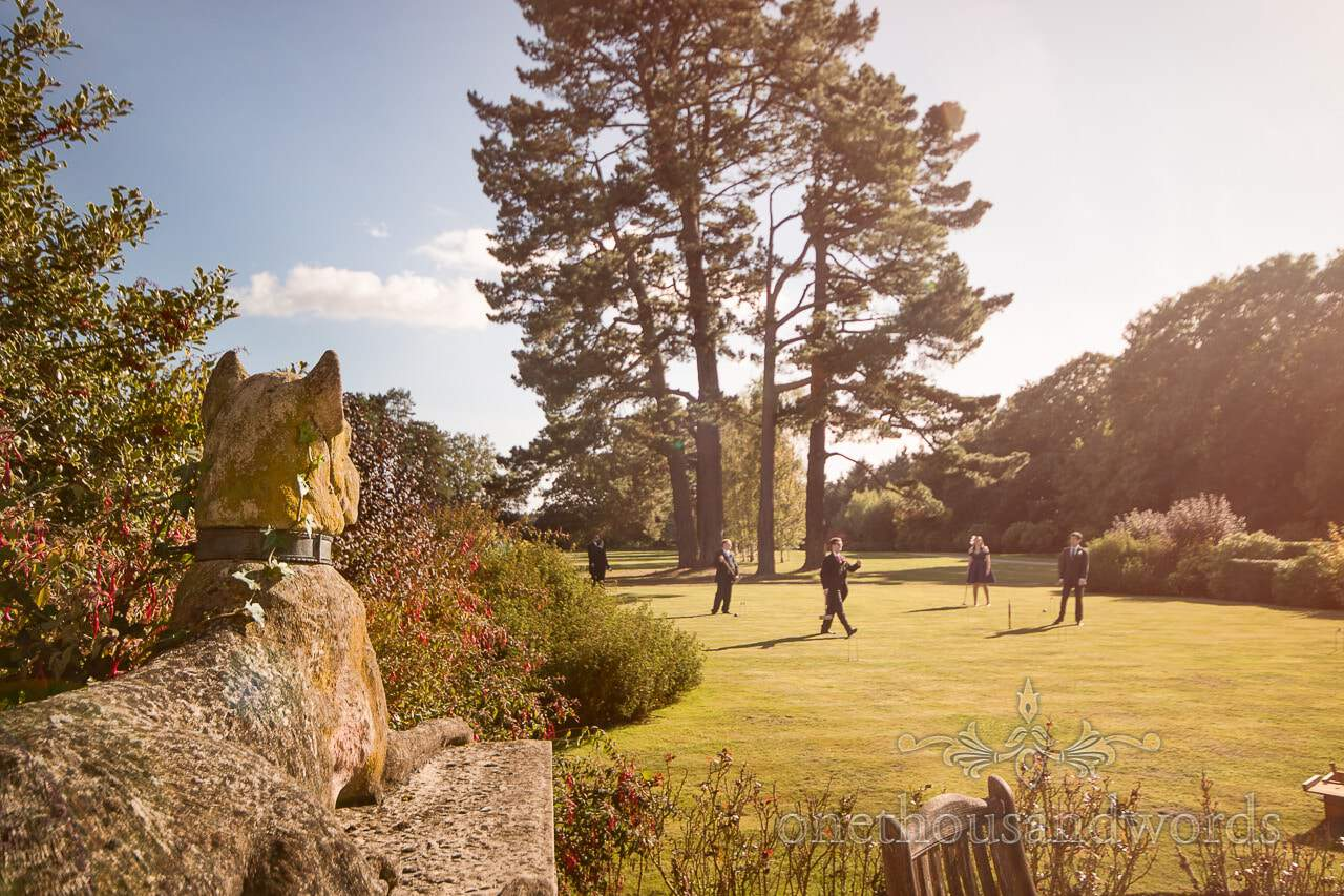 Stone dog sculpture overlooks wedding croquet at Hethfelton House