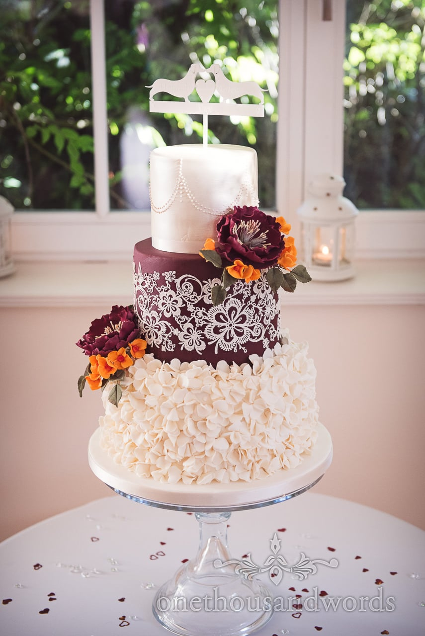 Three tier wedding cake with purple, orange and cream petal decoration