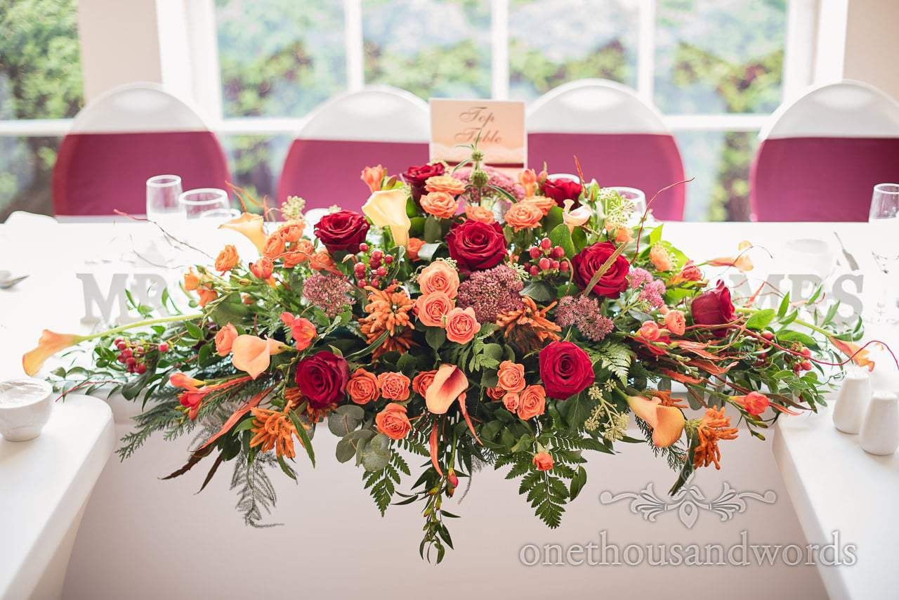 Top table flower spray with burgundy and orange at Hethfelton House