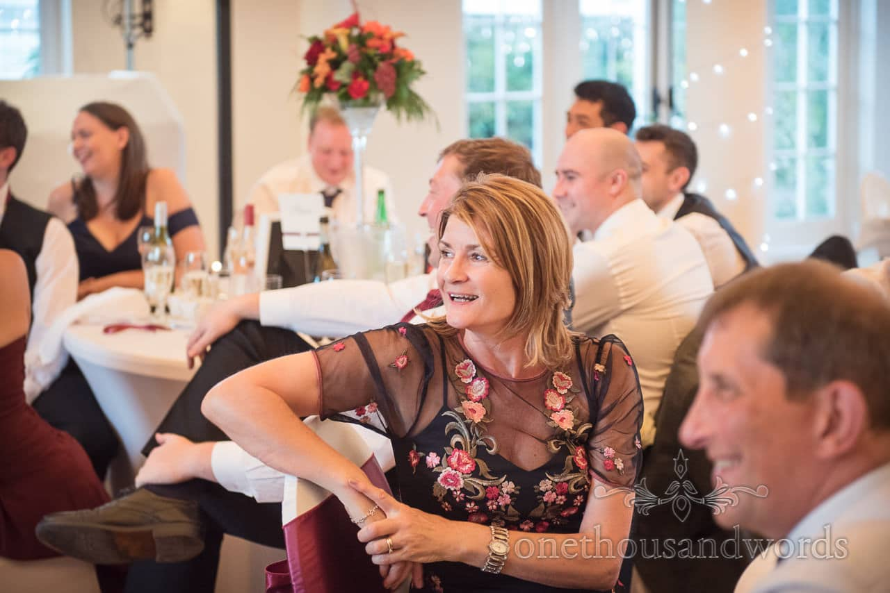 Wedding guest in floral dress laughs at wedding speeches