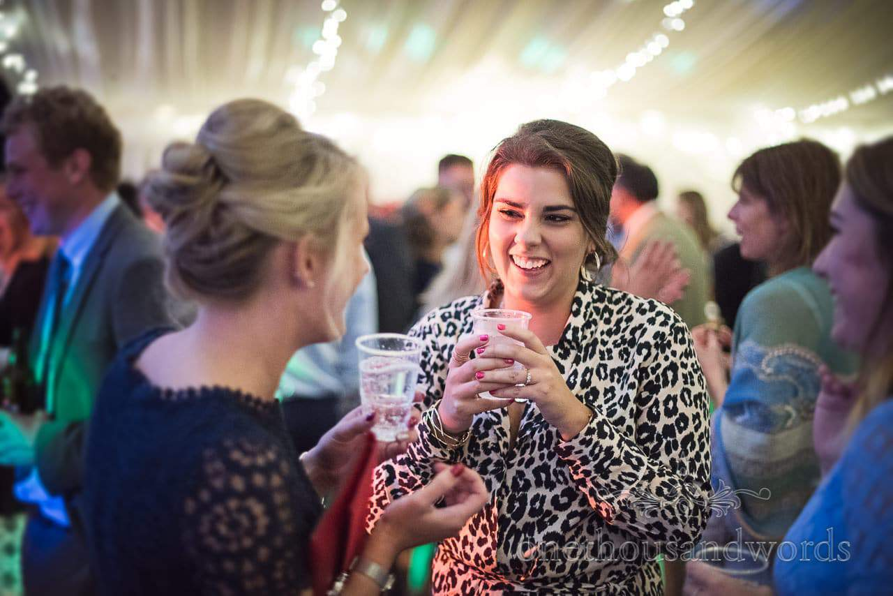Wedding guest in leopard print top laughing at marquee wedding reception