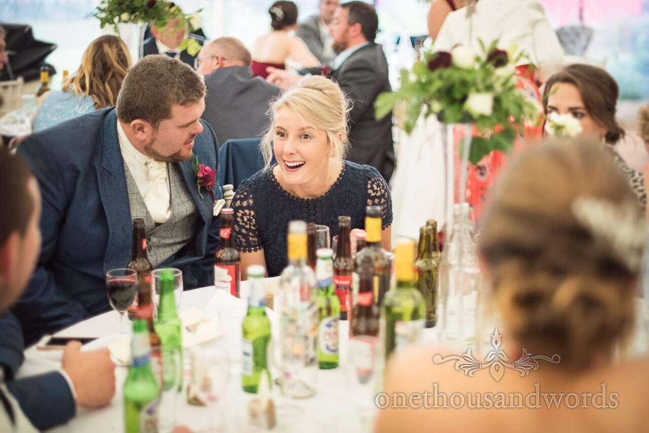 Wedding guest laughing at wedding breakfast tables in marquee