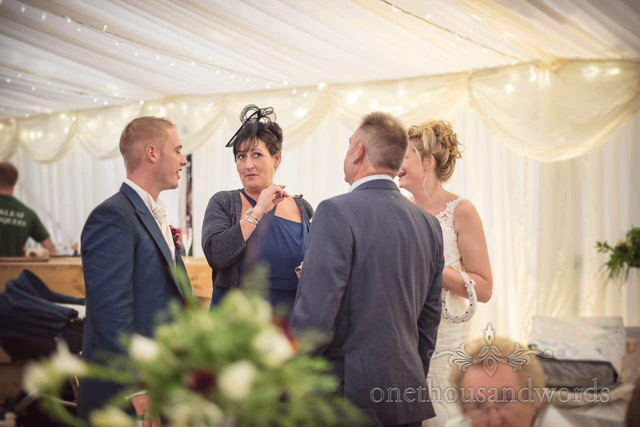 Wedding guest talks to bride and groomsmen at marquee wedding