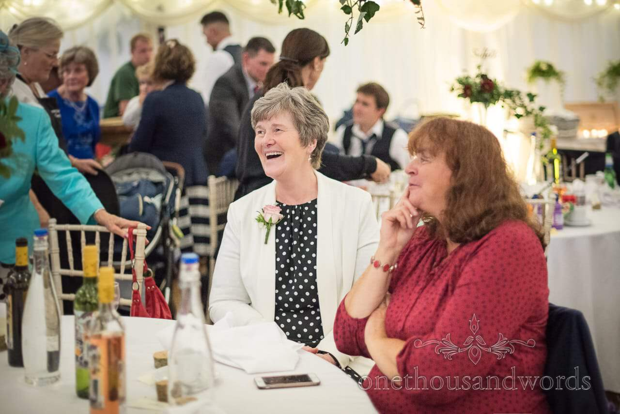 Wedding guests laughing during marquee evening reception