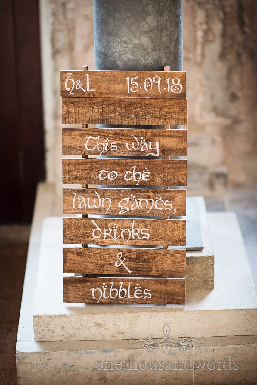 Wedding order of the day in Elven script on stained pallet wood at Lulworth Castle