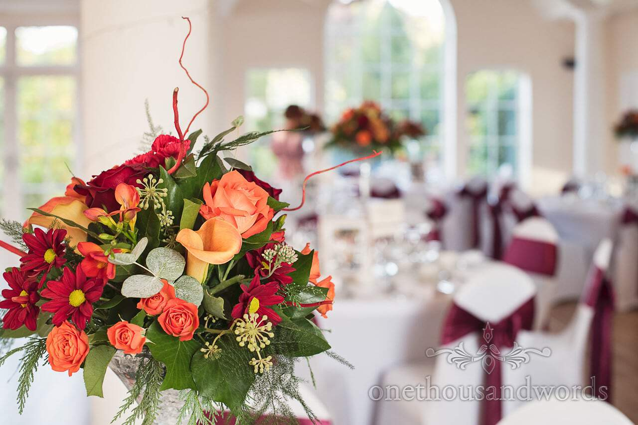Wedding table flower spray with burgundy and orange at Hethfelton