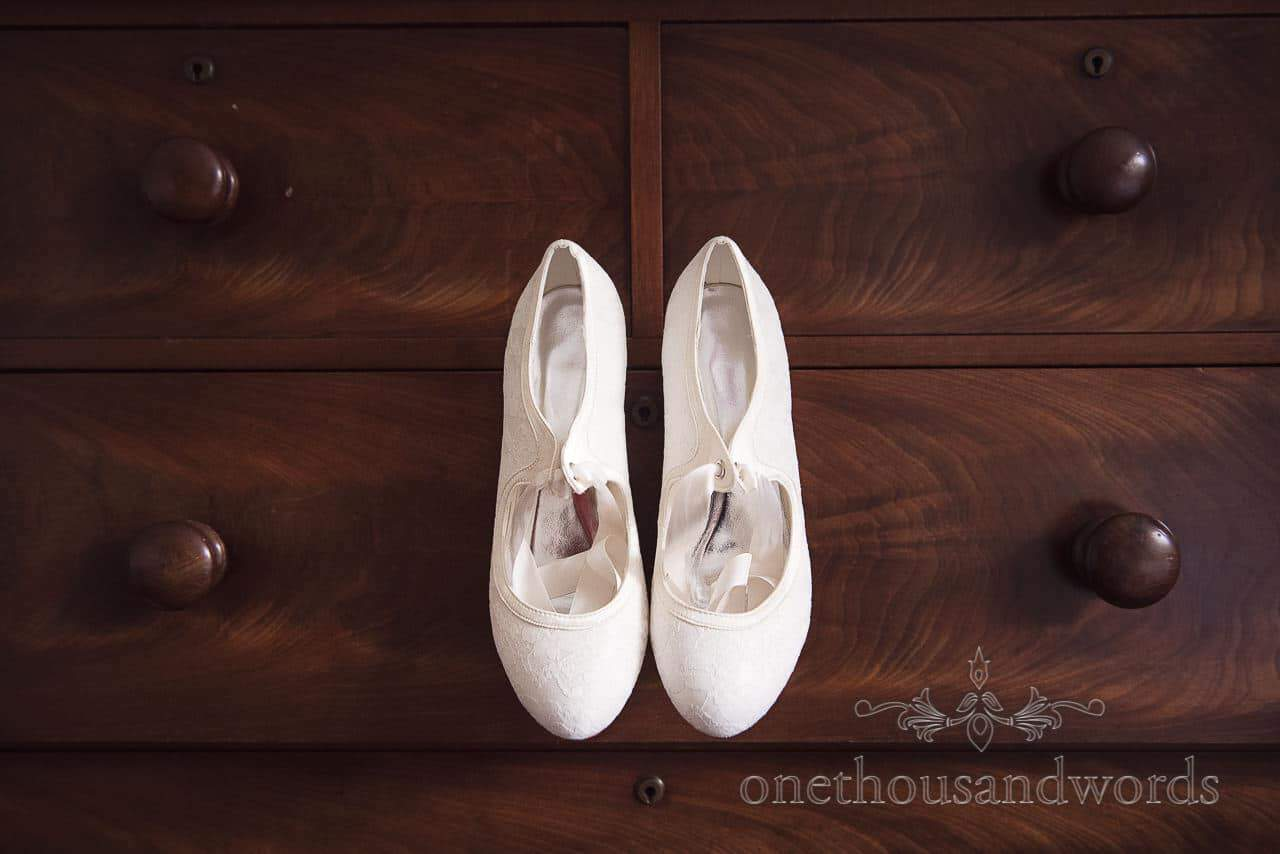 White bridal shoe hand on drawer on wedding morning