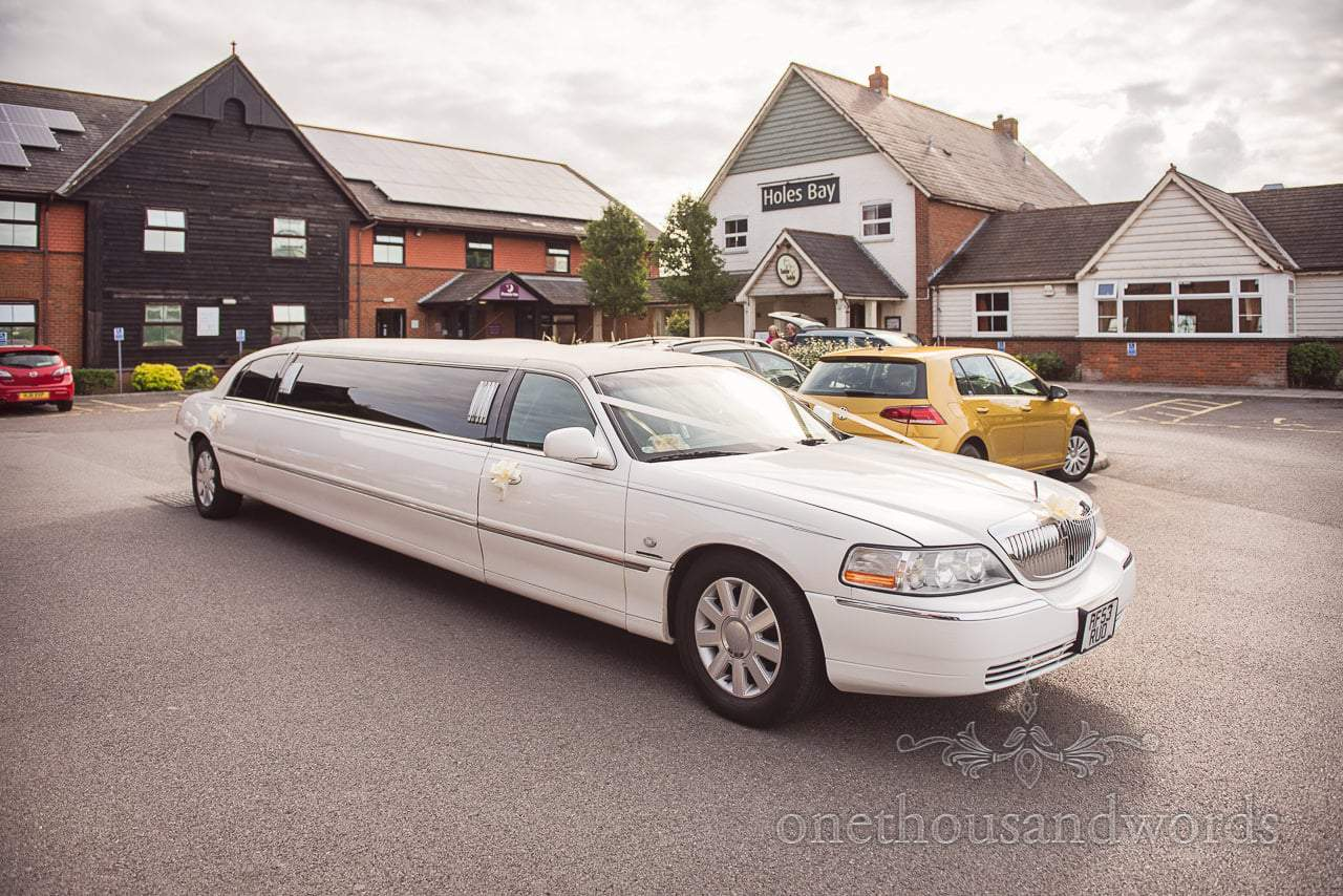White stretch limousine waits to transport the grooms party to Italian Villa wedding