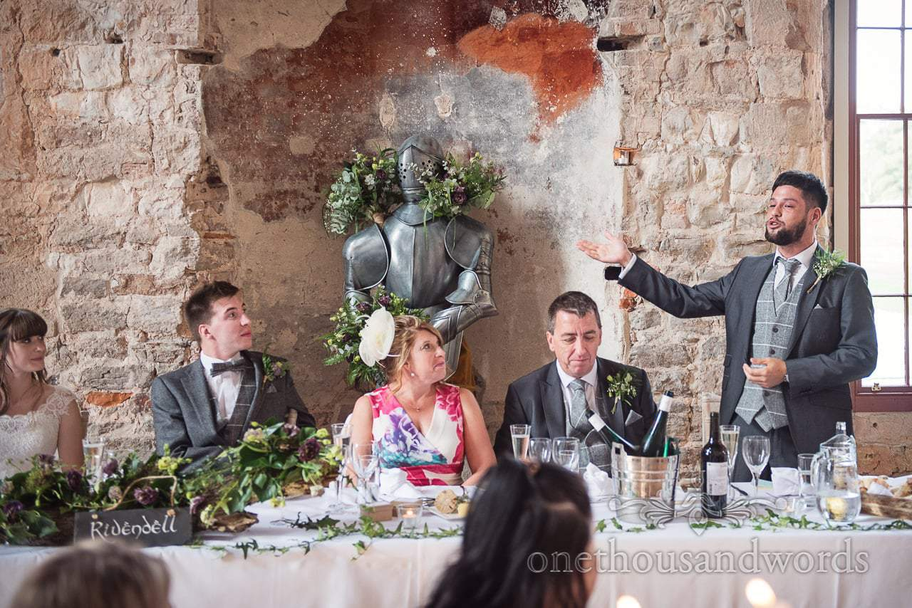 Woodland Lulworth Castle wedding photo of animated best man during speech