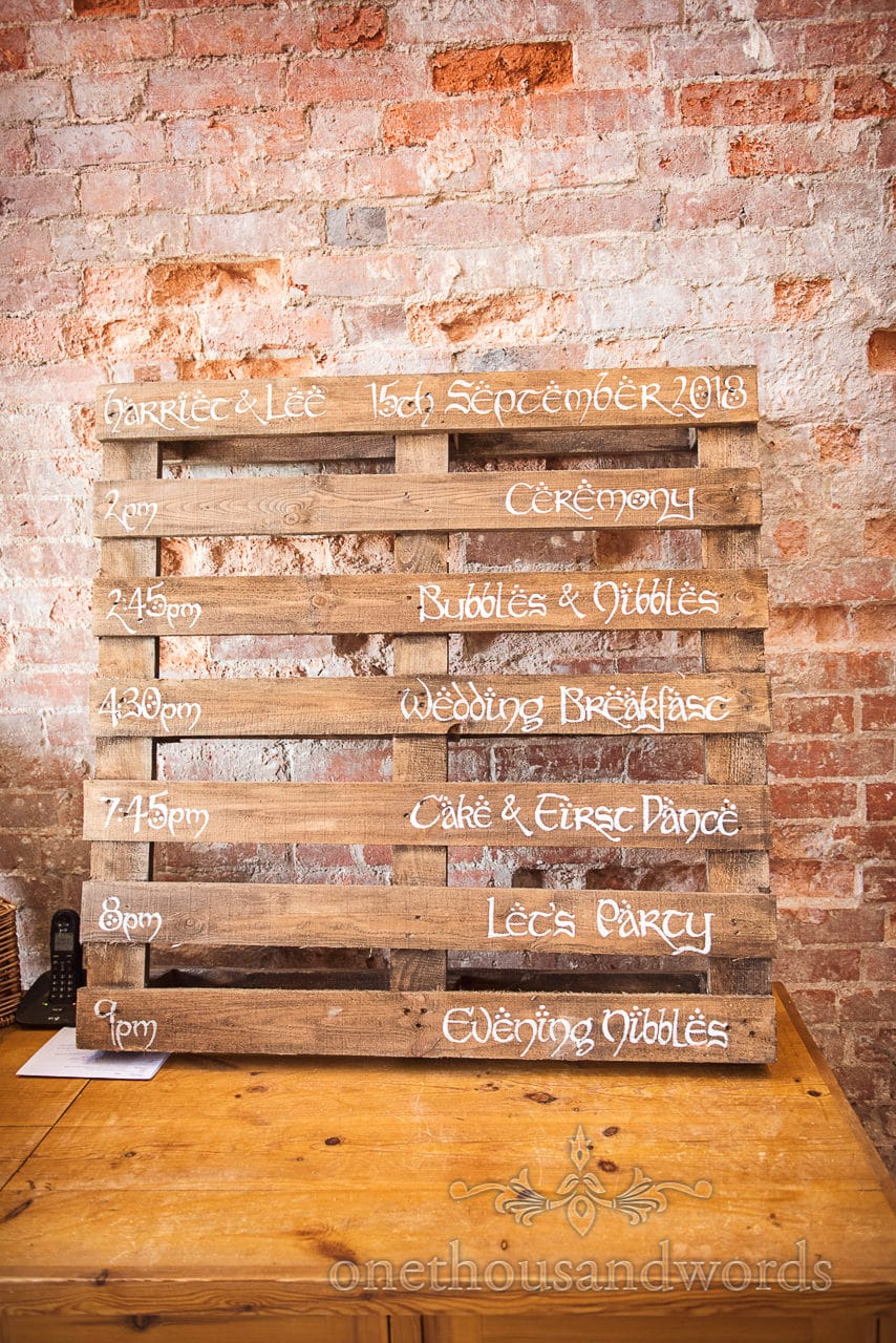 Woodland Lulworth Castle wedding photo of pallet wood order of day in calligraphy