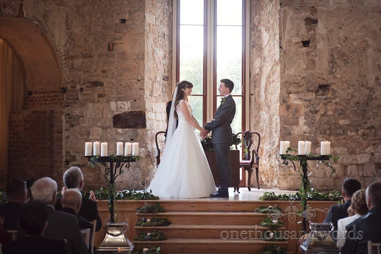 Woodland Lulworth Castle wedding photos of bride and groom holding hands