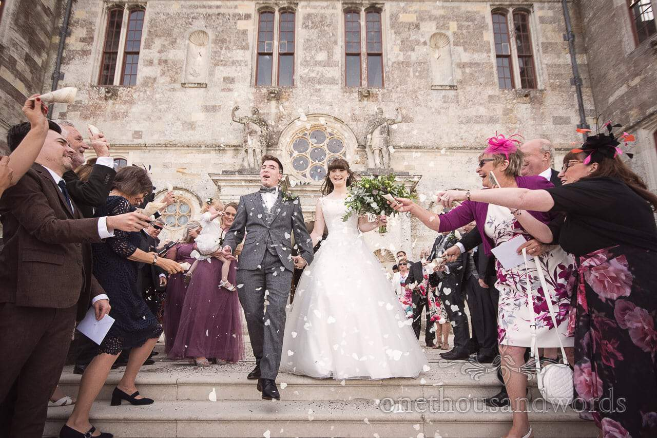 Woodland Lulworth Castle wedding photos of confetti shower on stairs