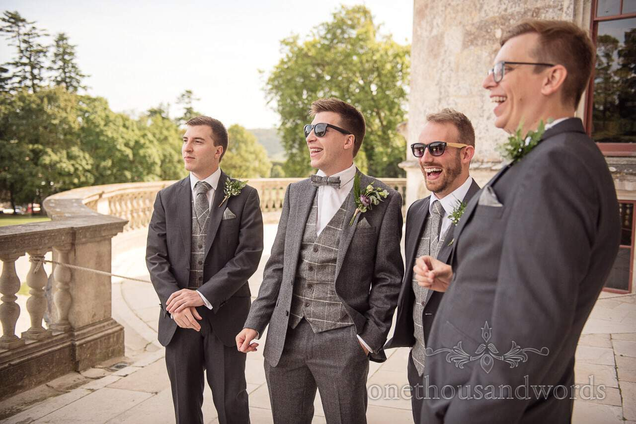 Woodland Lulworth Castle wedding Photos of groomsmen sharing a joke