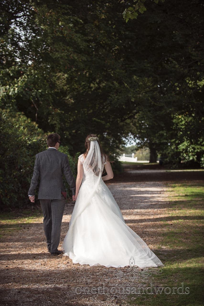 Woodland Lulworth Castle wedding photos of newlyweds taking a stroll