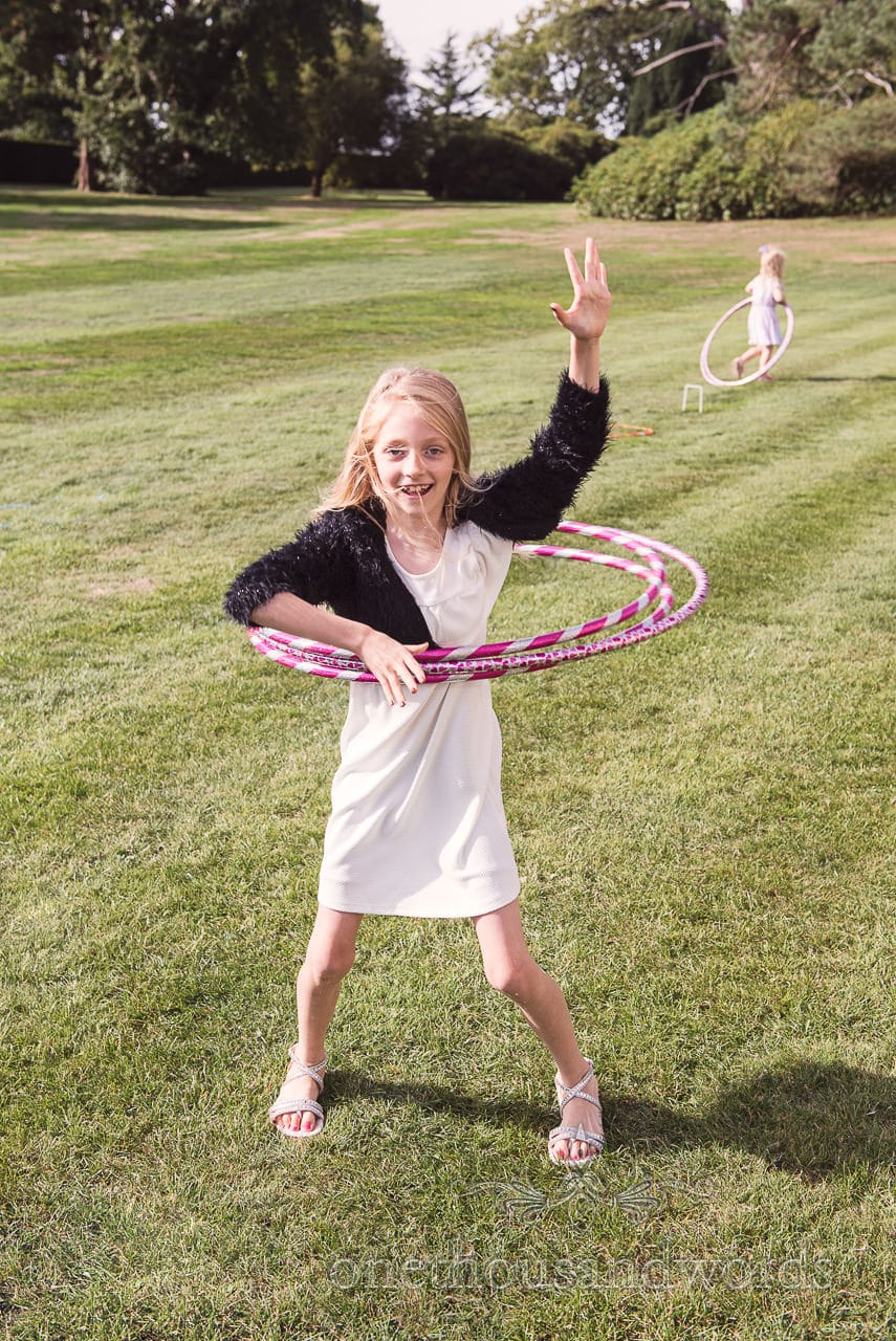 Young guest with three hula hoops at woodland Lulworth Castle wedding