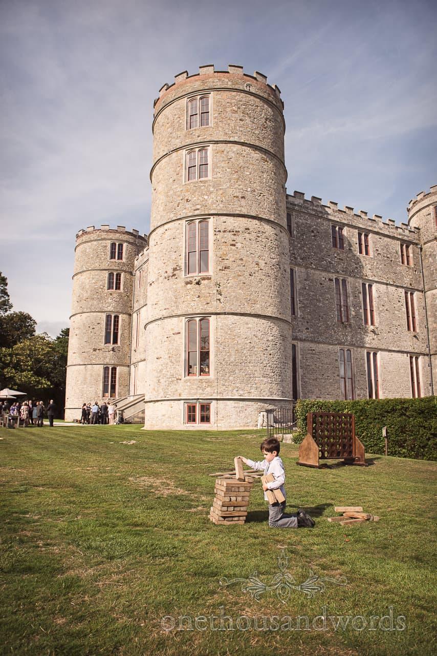 Young guests enjoys garden Jenga at woodland Lulworth Castle wedding