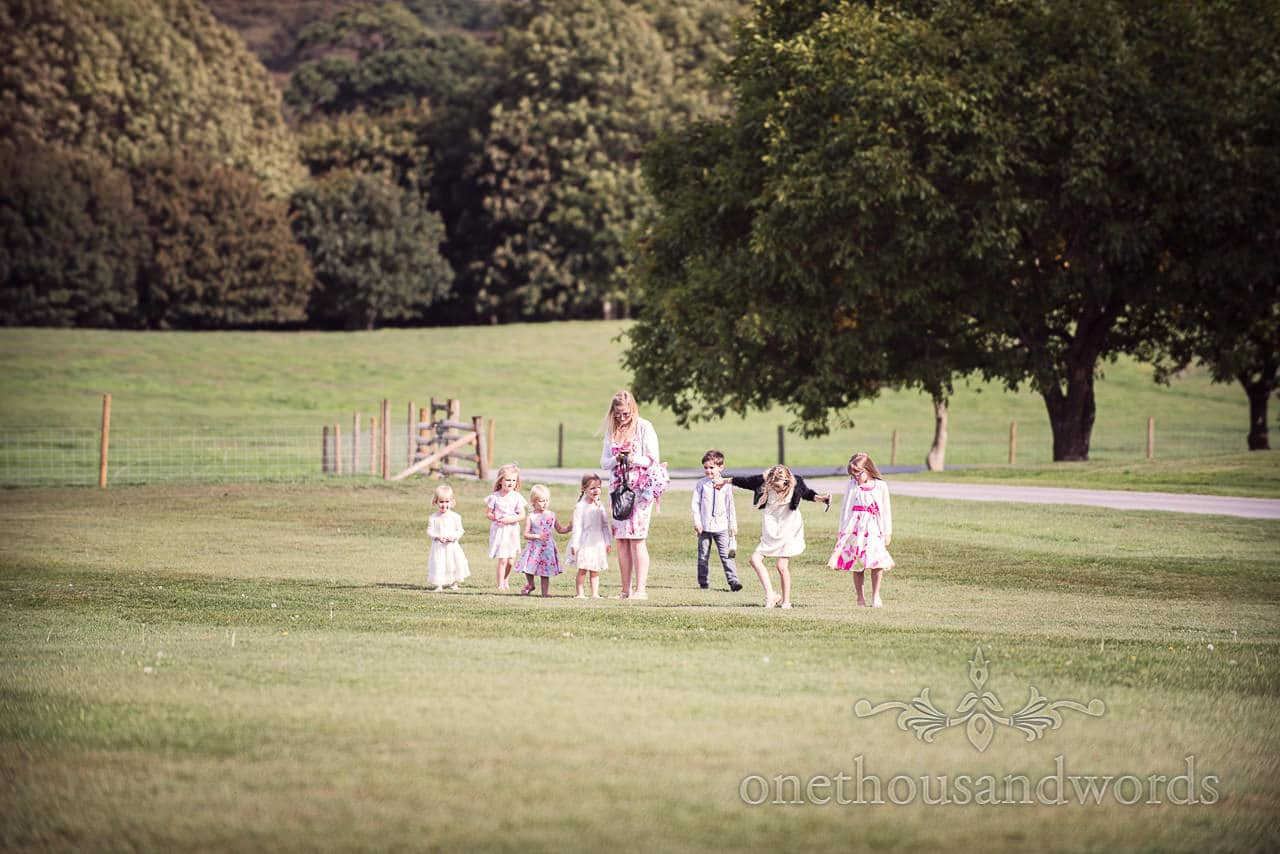 Younger guests explore field at woodland Lulworth Castle wedding