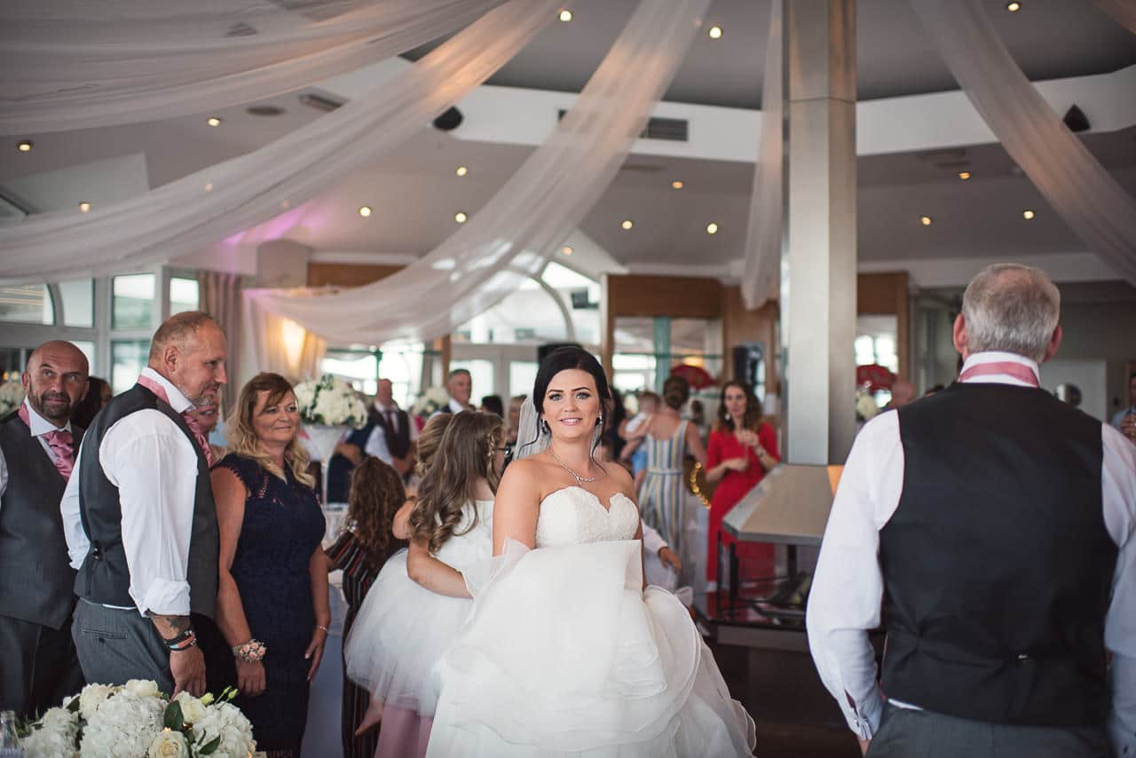 Beautiful bride in conga line at Sandbanks Hotel wedding breakfast room photo
