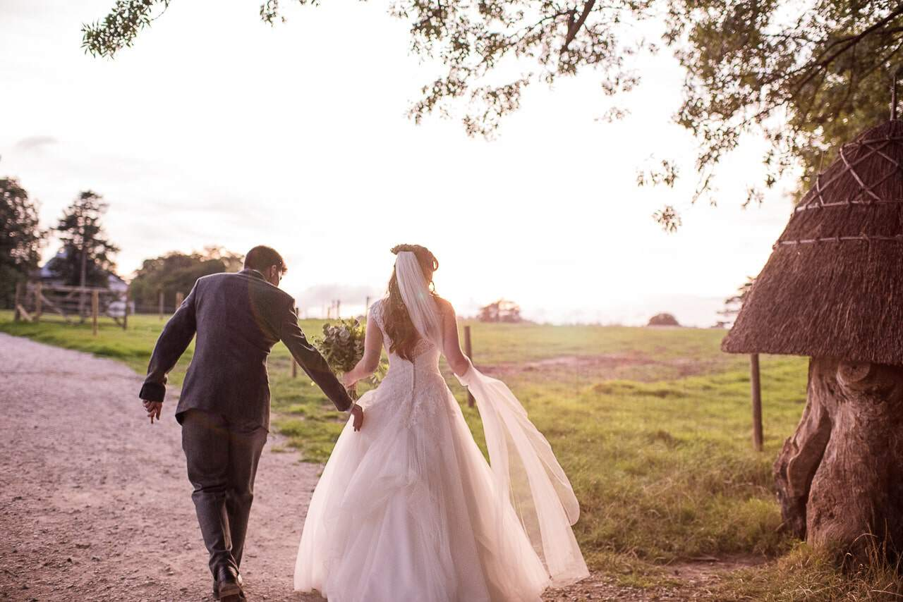 Bride and groom walk with sunset in Lulworth Castle countryside grounds