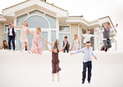 Child wedding guests jump from Sandbanks Hotel onto Dorset beach photograph