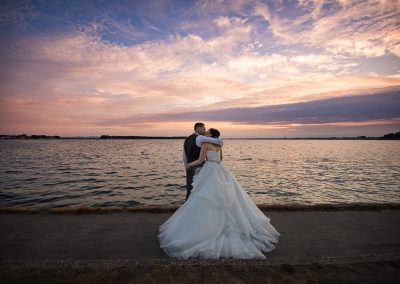Sunset over sea wedding couple kissing at Sandbanks Hotel wedding venue Dorset