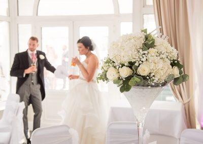 White and cream wedding flower bouquet in Martini vase at Sandbanks Hotel