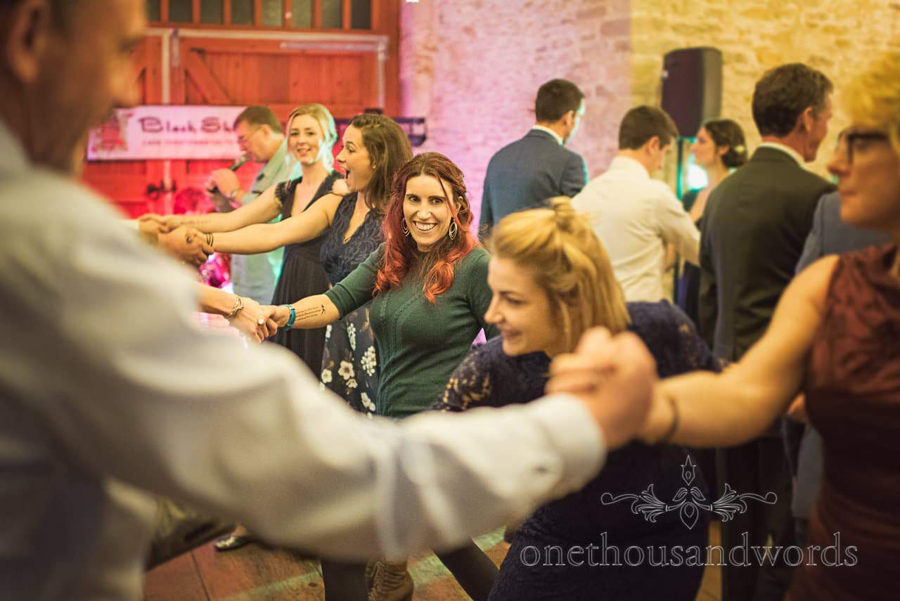 Barn dance wedding guests hold hands in line at Kingston Country Courtyard