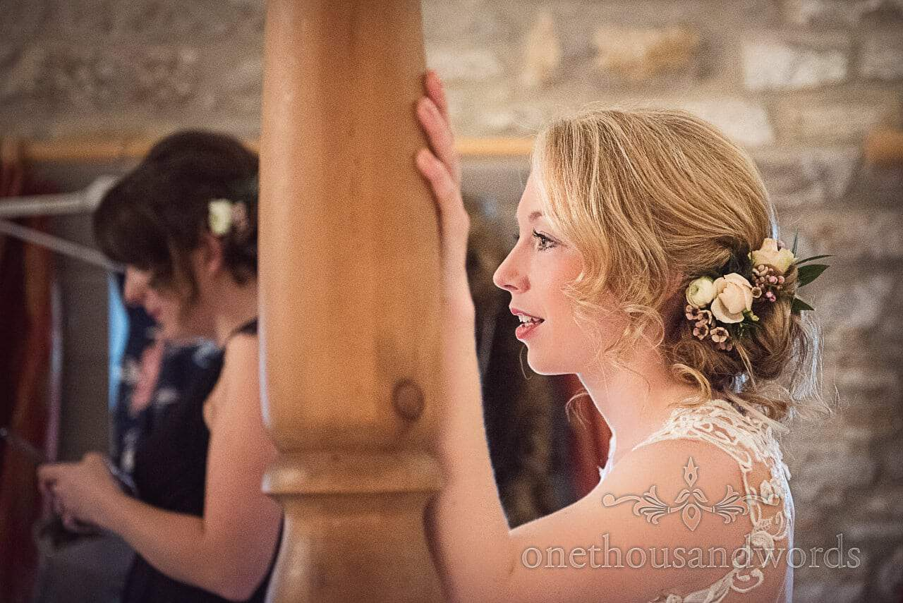 Beautiful blonde bride leans on bed post wedding morning portrait photograph