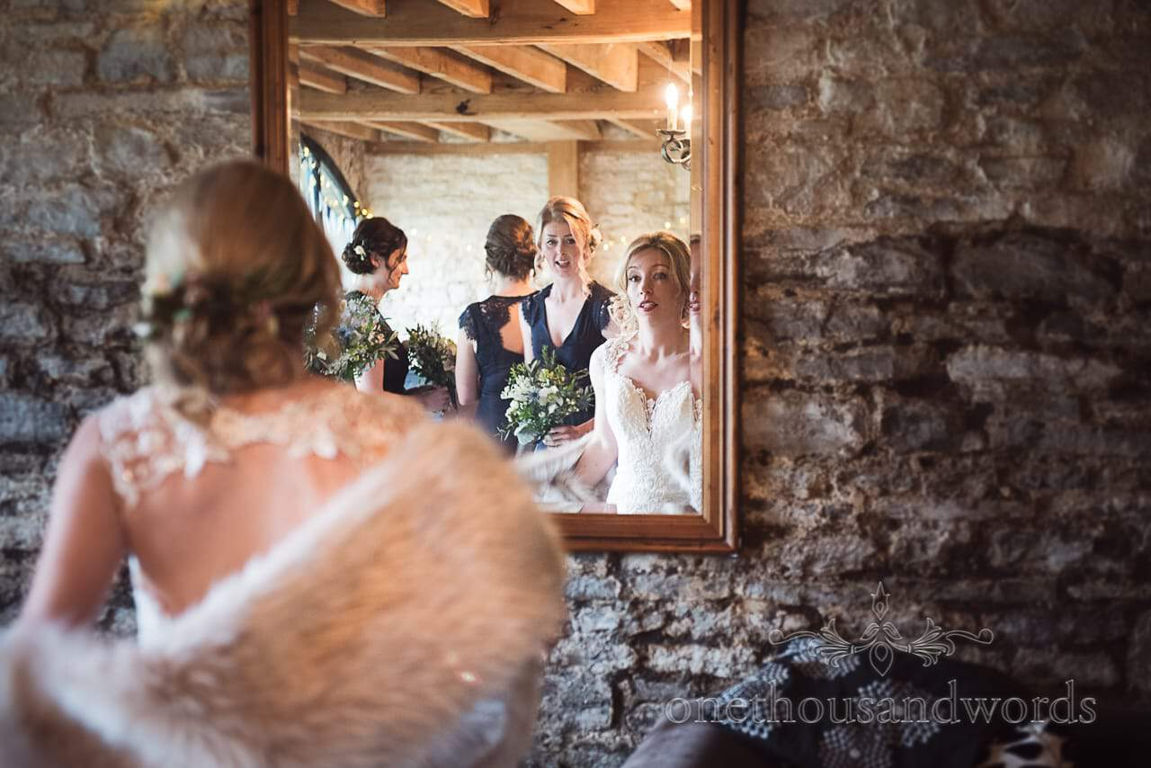 Beautiful blonde bride looks in mirror on stone wall with bridesmaids in blue dresses