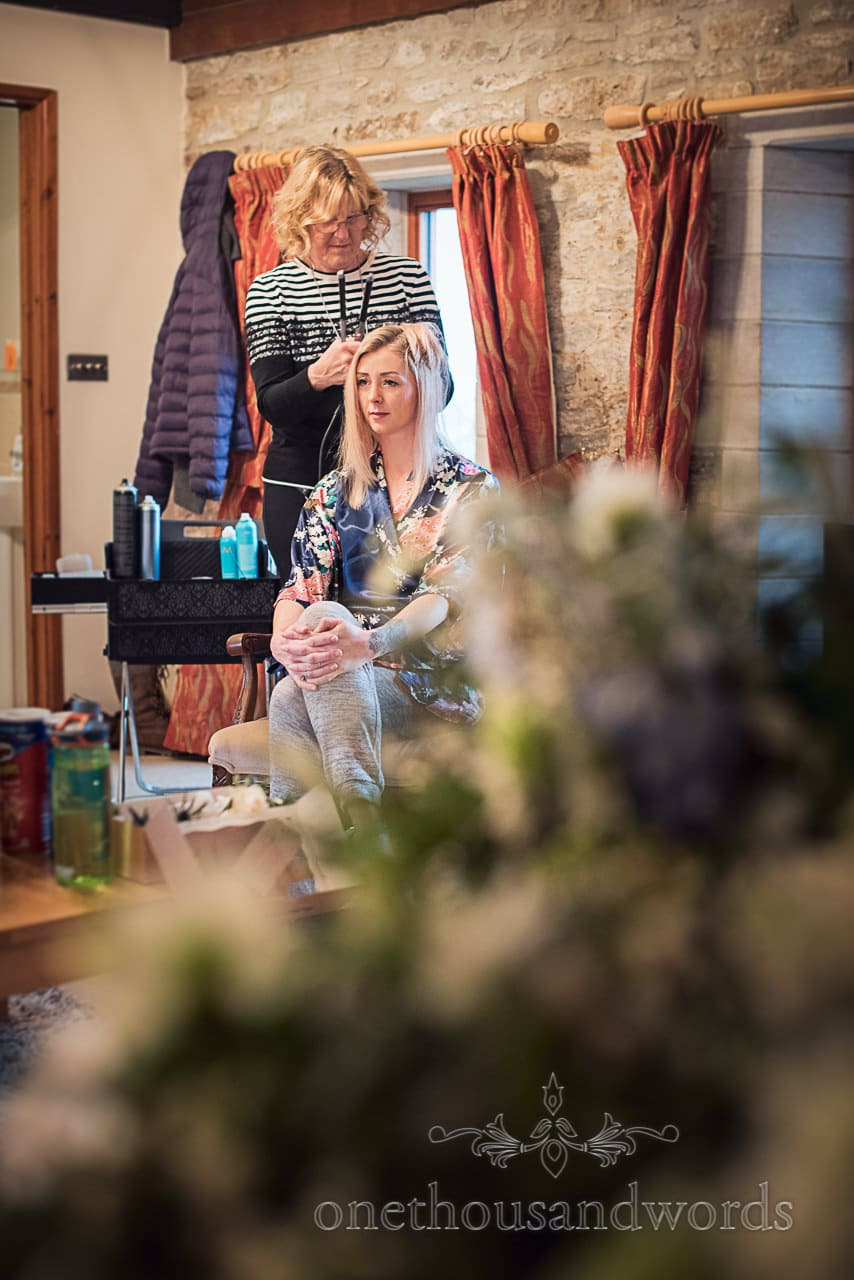 Blonde bridesmaid has wedding hair styled during bridal preparations at Dorset venue