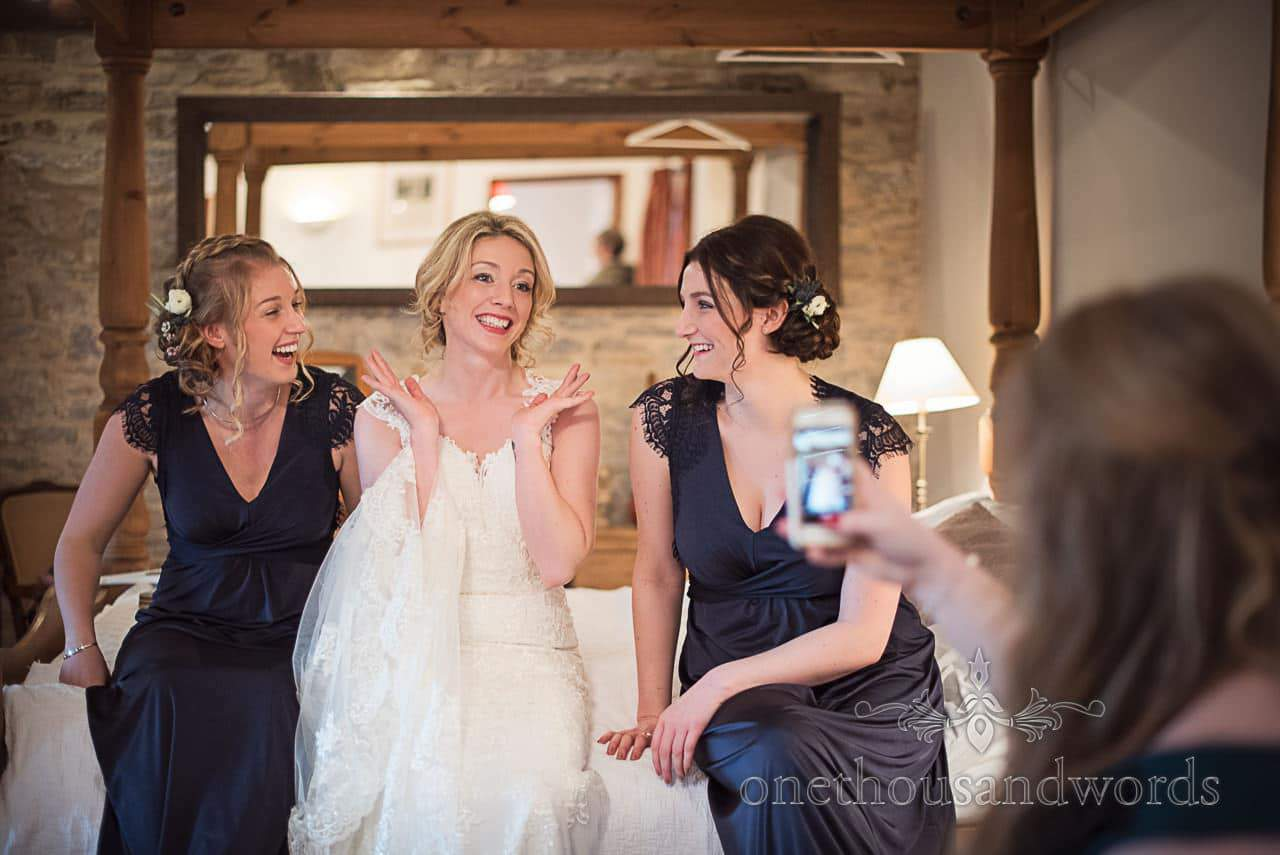 Bride and bridesmaids sit on bed to pose for photograph during bridal preparations