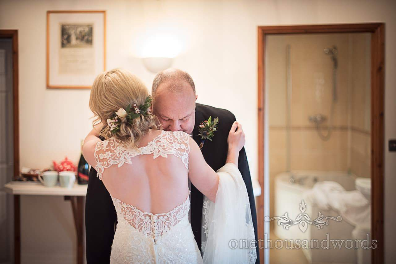 Bride in detailed white wedding dress hugs her father on wedding morning in Dorset
