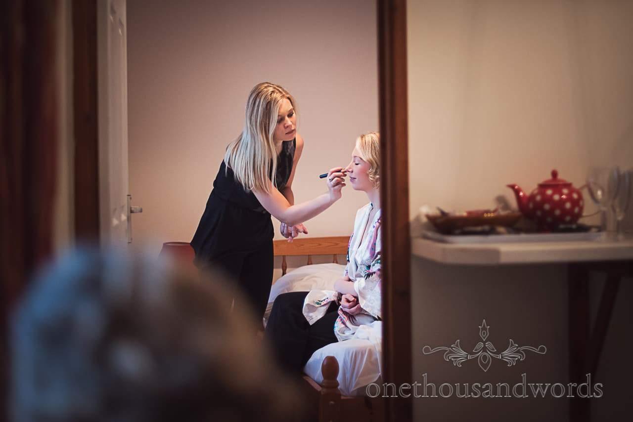 Bride in doorway has wedding makeup applied by wedding makeup artist