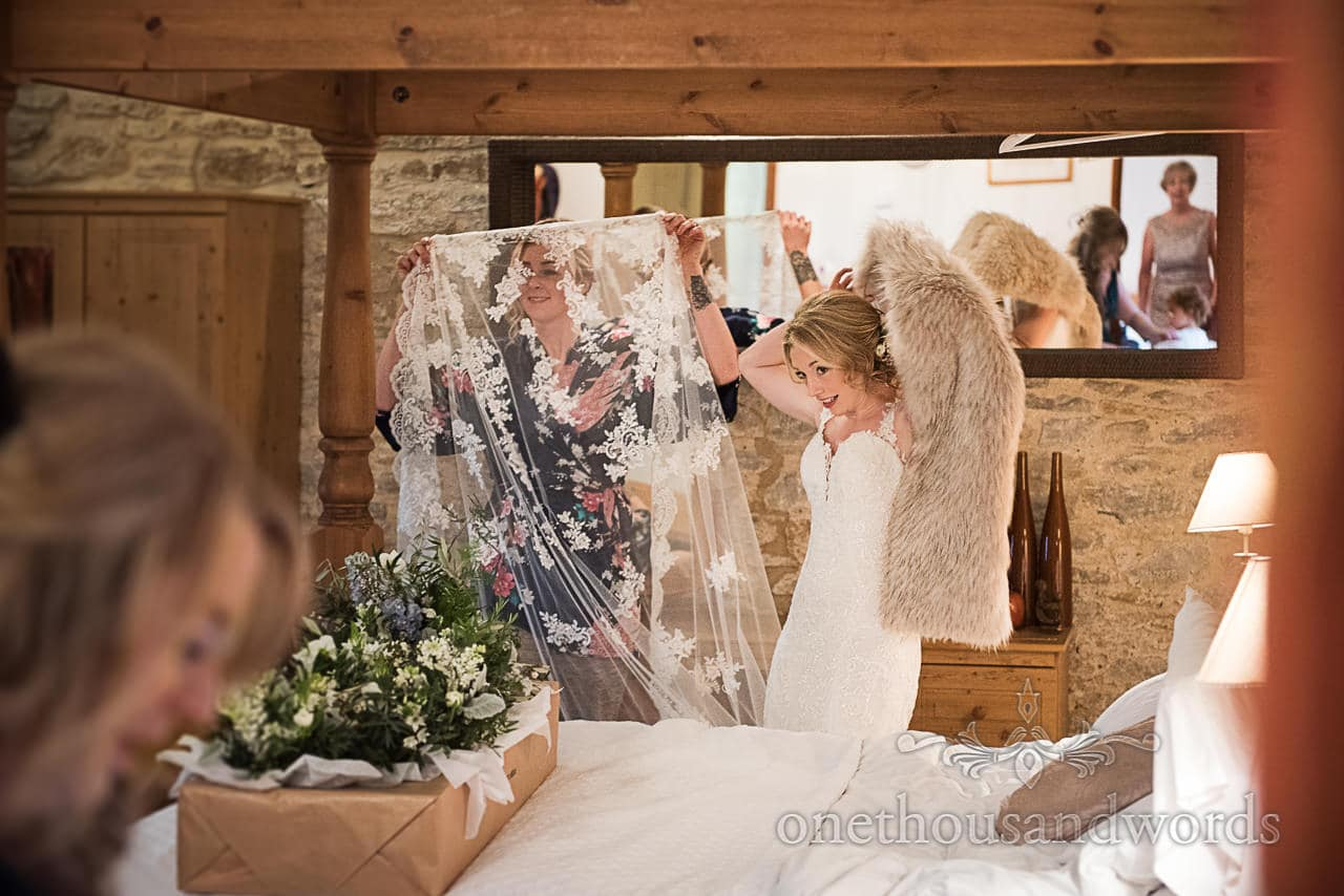 Bride puts on faux fur stole as bridesmaid examines lace detail on wedding train