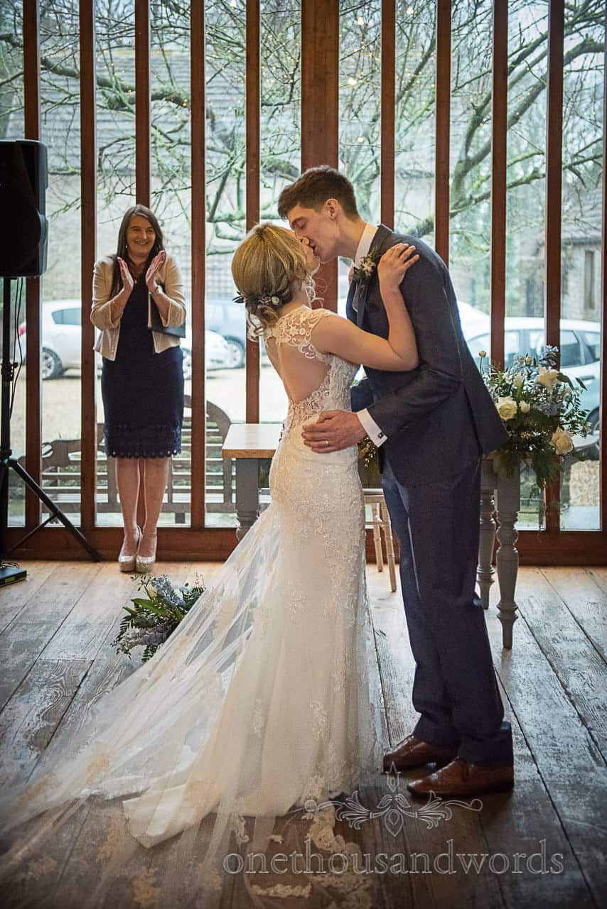 Bride and groom first kiss at Kingston Country Courtyard applauded by registrar