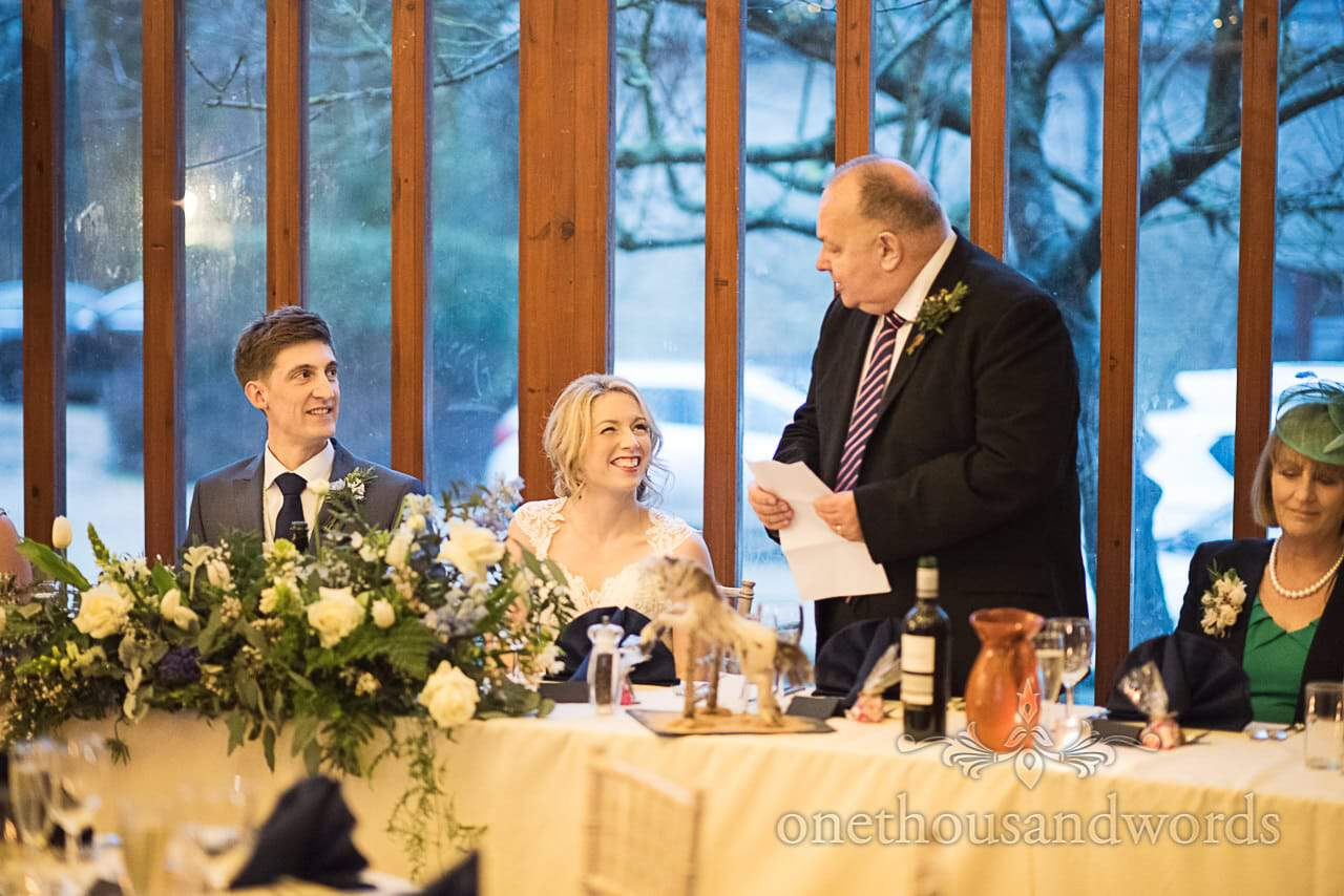 Bride and groom laughing at father of the bride speech at Dorset barn venue