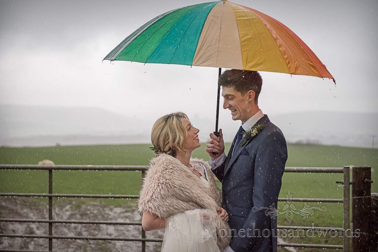 Bride and groom under rainbow umbrella in Dorset countryside rain