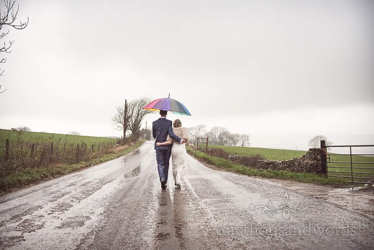 Bride and groom walk along Dorset country road under rainbow umbrella in rain