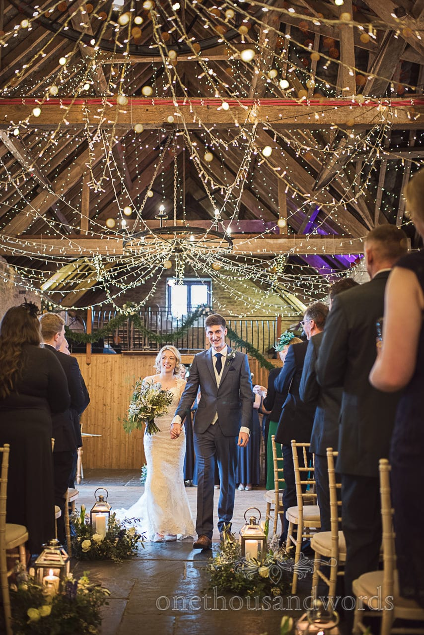 Bride and groom walk down the fairy lights barn aisle at Kingston Country Courtyard