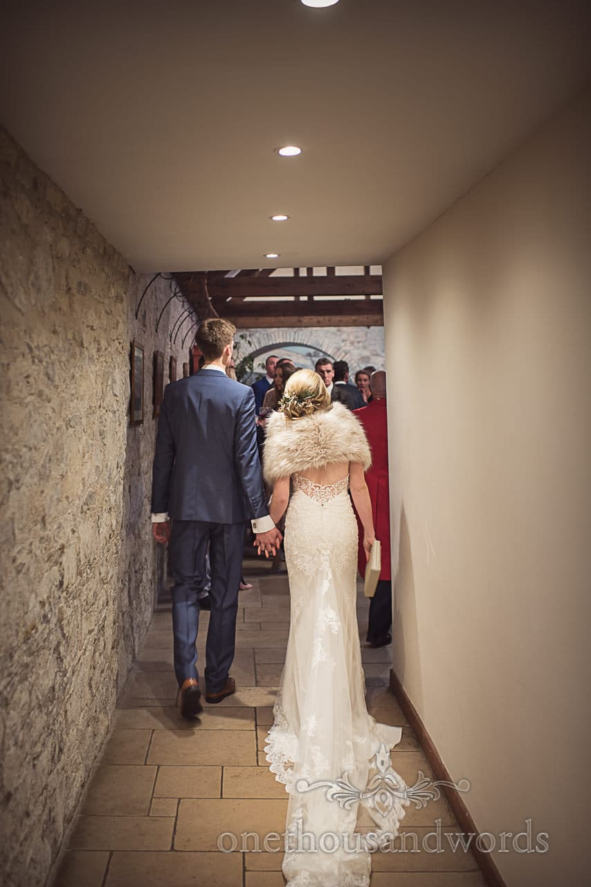 Bride and groom walk hand in hand to drinks reception at Kingston Country Courtyard