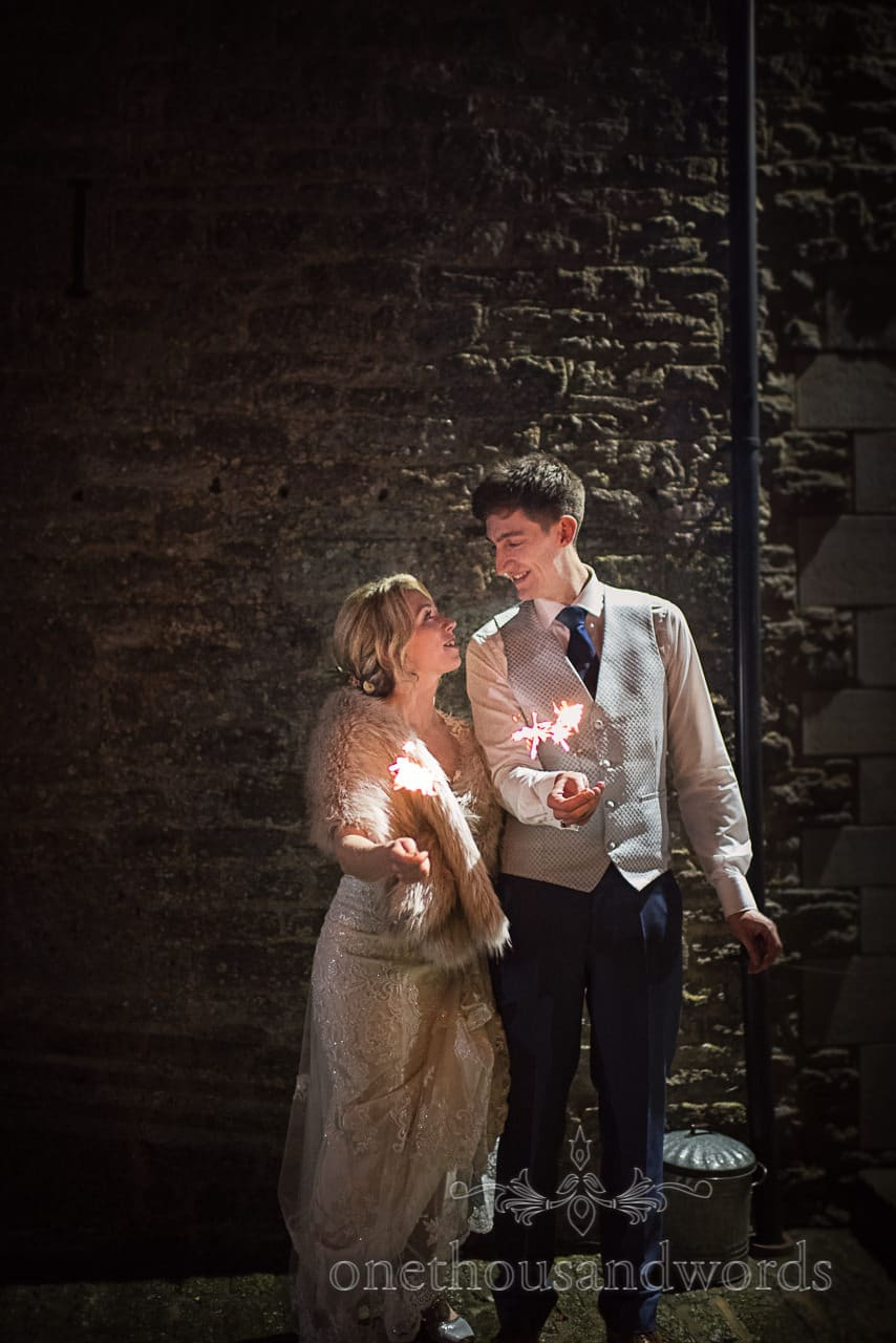 Bride and groom with wedding sparklers against stone wall in Kingston Dorset